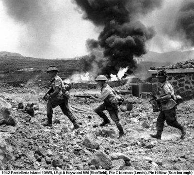 1942 Pantelleria Island 1DWR Soldiers running past a burning petrol dump