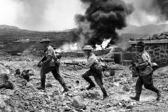 1942 Pantelleria Island 1DWR Soldiers running past a burning petrol dump